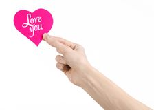 Valentine's Day and love theme: hand holds a greeting card in the form of a pink heart with the words Love you isolated. On white background Stock Images