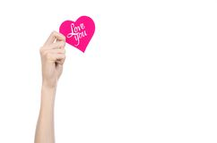 Valentine's Day and love theme: hand holds a greeting card in the form of a pink heart with the words Love you isolated Royalty Free Stock Photo