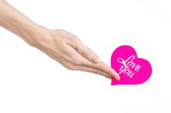Valentine's Day and love theme: hand holds a greeting card in the form of a pink heart with the words Love you isolated. On white background Royalty Free Stock Photos