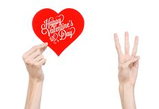 Valentine's Day and love theme: hand holds a greeting card in the form of a red heart with the words Happy Valentine's day Stock Photo