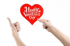 Valentine's Day and love theme: hand holds a greeting card in the form of a red heart with the words Happy Valentine's day Royalty Free Stock Images