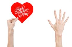 Valentine's Day and love theme: hand holds a greeting card in the form of a red heart with the words Happy Valentine's day Royalty Free Stock Image