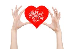 Valentine's Day and love theme: hand holds a greeting card in the form of a red heart with the words Happy Valentine's day Royalty Free Stock Photos