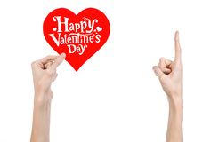 Valentine's Day and love theme: hand holds a greeting card in the form of a red heart with the words Happy Valentine's day Stock Image