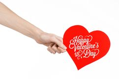 Valentine's Day and love theme: hand holds a greeting card in the form of a red heart with the words Happy Valentine's day. Isolated on white background, studio Stock Images
