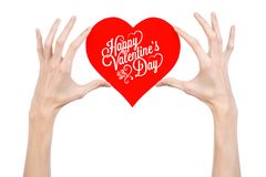 Valentine's Day and love theme: hand holds a greeting card in the form of a red heart with the words Happy Valentine's day Stock Photos