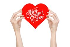 Valentine's Day and love theme: hand holds a greeting card in the form of a red heart with the words Happy Valentine's day Royalty Free Stock Photo