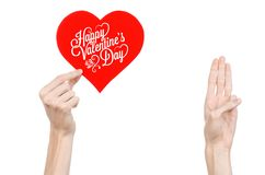 Valentine's Day and love theme: hand holds a greeting card in the form of a red heart with the words Happy Valentine's day Stock Images
