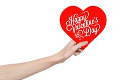 Valentine's Day and love theme: hand holds a greeting card in the form of a red heart with the words Happy Valentine's day. Isolated on white background, studio Royalty Free Stock Photography