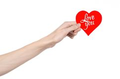 Valentine's Day and love theme: hand holds a greeting card in the form of a red heart with the words Love you isolated. On white background Royalty Free Stock Photo