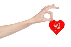 Valentine's Day and love theme: hand holds a greeting card in the form of a red heart with the words Love you isolated. On white background Royalty Free Stock Photos