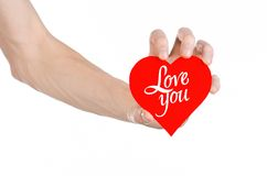 Valentine's Day and love theme: hand holds a greeting card in the form of a red heart with the words Love you isolated. On white background Royalty Free Stock Images