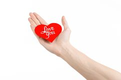 Valentine's Day and love theme: hand holds a greeting card in the form of a red heart with the words Love you isolated Stock Images