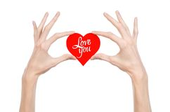 Valentine's Day and love theme: hand holds a greeting card in the form of a red heart with the words Love you isolated. On white background Royalty Free Stock Photography