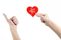 Valentine's Day and love theme: hand holds a greeting card in the form of a red heart with the words Love you isolated Stock Photo