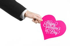 Valentine's Day and love theme: man's hand in a black suit holding a card in the form of a pink heart Royalty Free Stock Photography