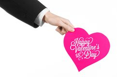 Valentine's Day and love theme: man's hand in a black suit holding a card in the form of a pink heart Royalty Free Stock Photos