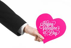 Valentine's Day and love theme: man's hand in a black suit holding a card in the form of a pink heart Stock Photo