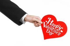 Valentine's Day and love theme: man's hand in a black suit holding a card in the form of a red heart Royalty Free Stock Image
