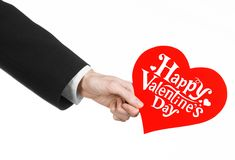 Valentine's Day and love theme: man's hand in a black suit holding a card in the form of a red heart Royalty Free Stock Photos