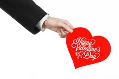 Valentine's Day and love theme: man's hand in a black suit holding a card in the form of a red heart Stock Photo