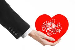 Valentine's Day and love theme: man's hand in a black suit holding a card in the form of a red heart Stock Photos