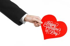 Valentine's Day and love theme: man's hand in a black suit holding a card in the form of a red heart Stock Image