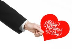 Valentine's Day and love theme: man's hand in a black suit holding a card in the form of a red heart Royalty Free Stock Photo