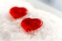 Valentine`s day two hearts in winter in the snow. Valentine`s day love two red hearts on snow in winter Stock Photos