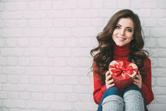 Valentine's Day. Lovely girl with a gift box heart. Portrait of a beautiful woman with long curly hair. Hair and make-up Royalty Free Stock Photos