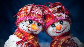 Valentine`s Day. Lovers of snowmen are in the snow and keep the hearts of the fabric. Valentine`s Day. Snowmen love couple set against each other. Snowmen in stock video