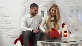 Valentine`s Day. Man giving a gift in a box to his sad girlfriend sitting on sofa. stock footage