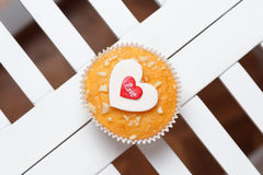 Valentine's day muffin. With red and white hearts on a white wooden table Stock Image