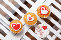 Valentine's day muffins. With red and white hearts on a white wooden table with a note Stock Images