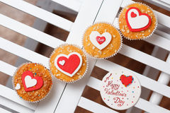 Valentine's day muffins. With red and white hearts on a white wooden table with a note Stock Photography