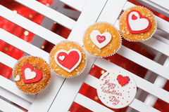 Valentine's day muffins. With red and white hearts on a white wooden table with a note Royalty Free Stock Photo