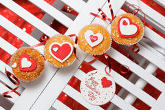 Valentine's day muffins. With red and white hearts on a white wooden table with a note and ribbon Stock Photography