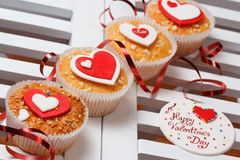 Valentine's day muffins. With red and white hearts on a white wooden table with a note and ribbon Royalty Free Stock Photography