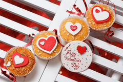 Valentine's day muffins. With red and white hearts on a white wooden table with a note and ribbon Stock Image