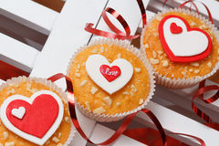 Valentine's day muffins. With red and white hearts on a white wooden table with a note and ribbon Royalty Free Stock Image