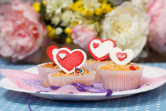 Valentine's day muffins. White plate with valentine's day muffins with red and white hearts on a blue with dots (polka dot) table and flowers on the background Stock Photography
