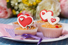 Valentine's day muffins. White plate with valentine's day muffins with red and white hearts on a blue with dots (polka dot) table and flowers on the background Royalty Free Stock Photos