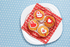 Valentine's day muffins. White plate with valentine's day muffins with red and white hearts on a blue in white dots background (polka dot Stock Photo