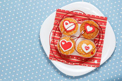 Valentine's day muffins. White plate with valentine's day muffins with red and white hearts on a blue in white dots background (polka dot Royalty Free Stock Photo