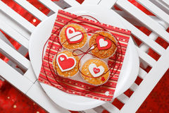 Valentine's day muffins. White plate with valentine's day muffins with red and white hearts on a white wooden table Stock Image