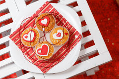 Valentine's day muffins. White plate with valentine's day muffins with red and white hearts on a white wooden table Royalty Free Stock Photo