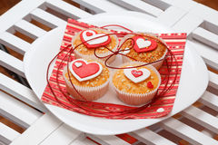 Valentine's day muffins. White plate with valentine's day muffins with red and white hearts on a white wooden table Royalty Free Stock Photography
