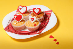 Valentine's day muffins. White plate with valentine's day muffins with red and white hearts on a yellow background Stock Photography