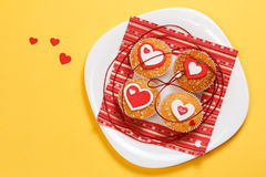 Valentine's day muffins. White plate with valentine's day muffins with red and white hearts on a yellow background Stock Image