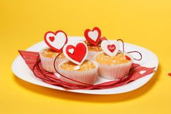 Valentine's day muffins. White plate with valentine's day muffins with red and white hearts  on a yellow background Royalty Free Stock Photos